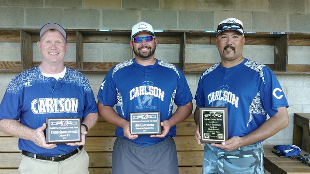 baseball coaches holding plaques in dugout