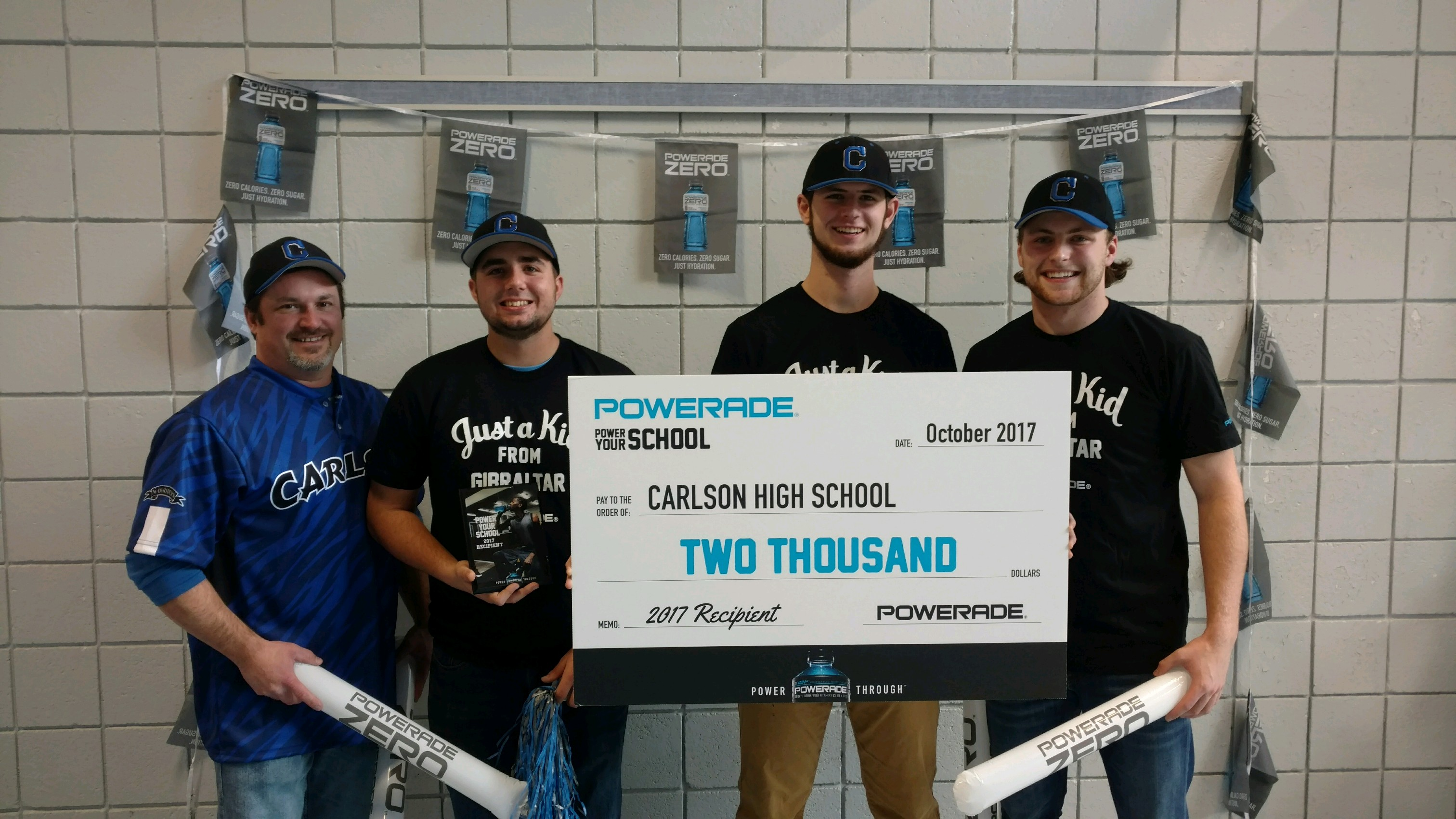 Three players and a coach hold a large check