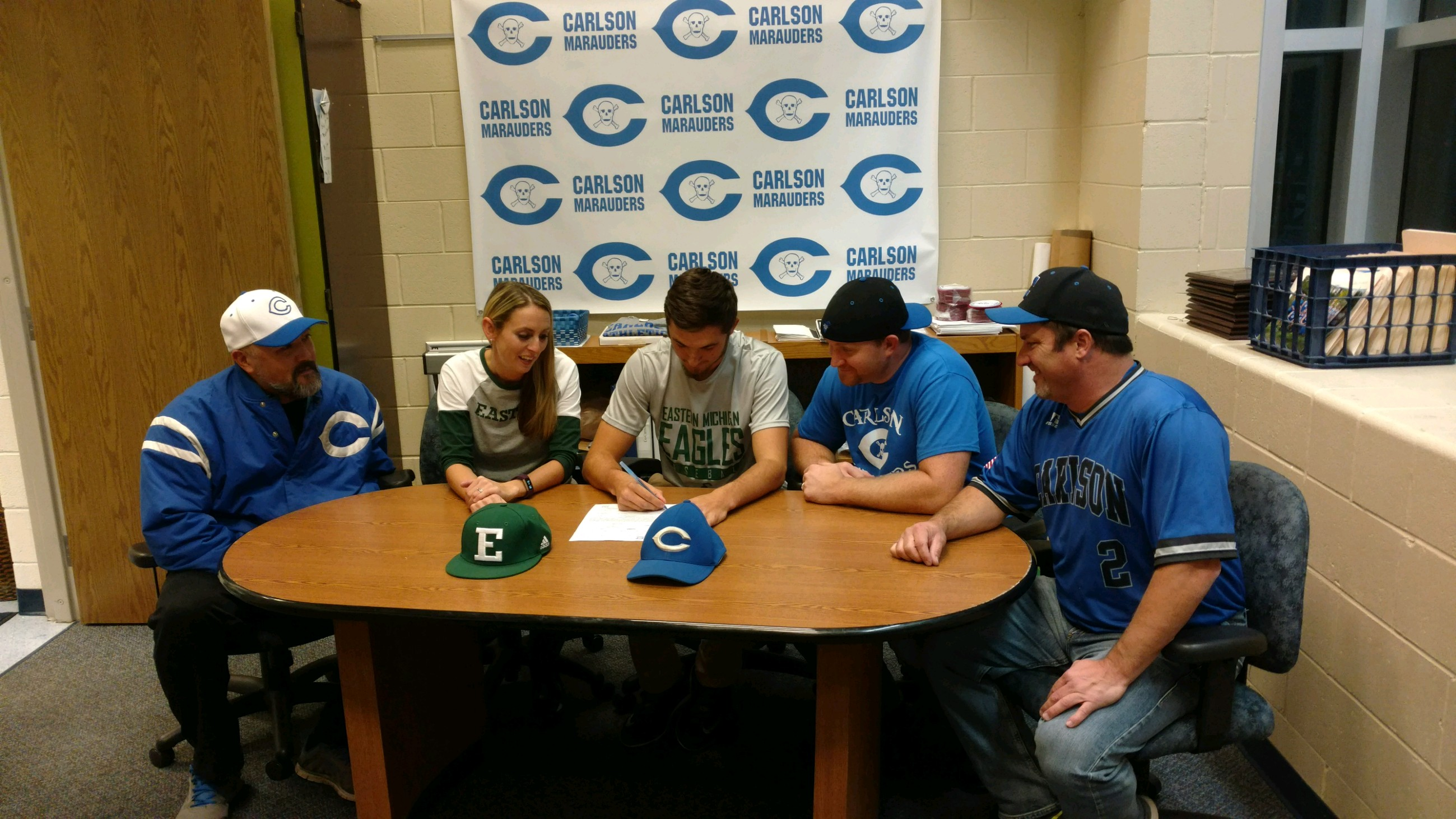 A player signs a letter with his coaches