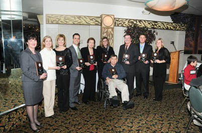 Ten people dressed formally and holding plaques
