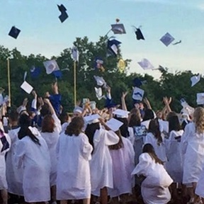 Graduating students throw hats in the air on a  sunny day